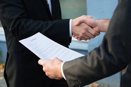 two men shaking hands over a contract